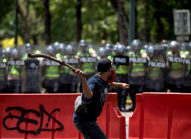 A student aims a stick of wood at Bolivarian National Police officers during clashes outside the Central University in Caracas, Venezuela, Thursday, June 9, 2016. Students had planned to march from Venezuela's top university to elections headquarters, but hundreds of police in riot gear blocked the way. Students covered their faces with Venezuelan flags and threw bottles, stones and sticks while police lobbed tear gas. (Photo by Fernando Llano/AP Photo)