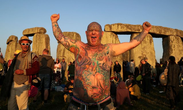 A reveler called Mad Alan (real name) celebrates the 2014 summer solstice, the longest day of the year, at sunrise at the prehistoric monument Stonehenge, near Amesbury in Southern England, on June 21, 2014. The festival, which dates back thousands of years, celebrates the longest day of the year when the sun is at its maximum elevation. Modern druids and people gather at the landmark Stonehenge every year to see the sun rise on the first morning of summer. (Photo by Geoff Caddick/AFP Photo)
