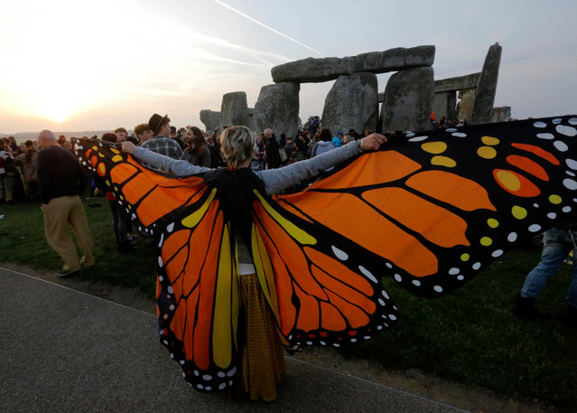 Reveler wearing butterfly wings waits for the sun to rise on the summer solstice during the annual festival at Stonehenge, Salisbury, Britain, 21 June 2017. (Photo by Kim Ludbrook/EPA)
