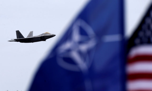 NATO and U.S. flags flutter as U.S. Air Force F-22 Raptor fighter flies over the military air base in Siauliai, Lithuania, April 27, 2016. (Photo by Ints Kalnins/Reuters)