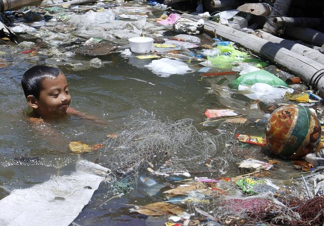 A boy swims in murky waters to cool off during a hot day outside his floating house along Manila Bay April 25, 2012