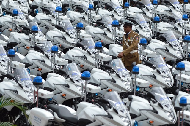 A Sri Lankan policeman stands next to new motorcycles at a ceremony in Colombo on July 1, 2014 marking the official distribution of 279 high-powered units to traffic constables across the country. The 600cc Yamaha bikes were deployed to bolster traffic police in a country where over 2,500 people are killed annually in road accidents, making Sri Lankan roads among the world's deadliest. (Photo by Ishara S. Kodikara/AFP Photo)