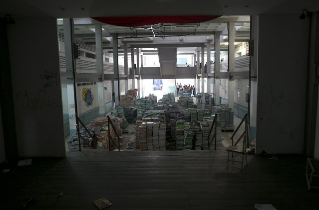 In this May 31, 2016 photo, a pile of 30,000 unopened textbooks block the auditorium stage, a favorite make-out spot for students at a public high school in Caracas, Venezuela. The government delivered the books at the start of the year, but teachers decided they were too full of pro-socialist propaganda to use. (Photo by Ariana Cubillos/AP Photo)