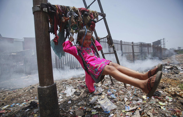 Sana, a five-year-old girl, plays on a cloth sling hanging from a signalling pole as smoke from a garbage dump rises next to a railway track in Mumbai