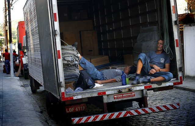 """Movers rest during their lunch break in the neighborhood of Santa Teresa in Rio de Janeiro, on June 24, 2014. In a project called """"On The Sidelines"""" Reuters photographers share pictures showing their own quirky and creative view of the 2014 World Cup in Brazil. (Photo by Kai Pfaffenbach/Reuters)"""