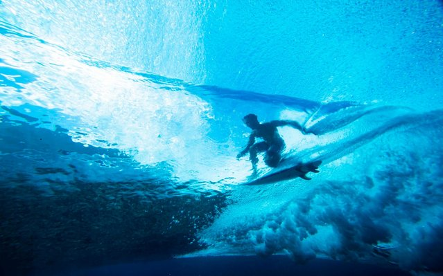 """Taumata Puhetini from Tahiti rides in the """"tube"""", shot from an underwater perspective, at Teahupoo a reef surfing break in Tahiti on August 15, 2019. The surfers are practicing for the Tahiti pro Trials. (Photo by Brian Bielmann/AFP Photo)"""