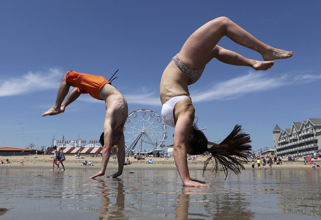 Dan Copeland, left, and Alex Morneau of Biddeford, Maine, former high school cheerleaders, perform back flips while enjoying the record breaking heat, Thursday, May 18, 2017, at Old Orchard Beach, Maine. The temperature climbed well into the 90s in many locations throughout the state. (Photo by Robert F. Bukaty/AP Photo)