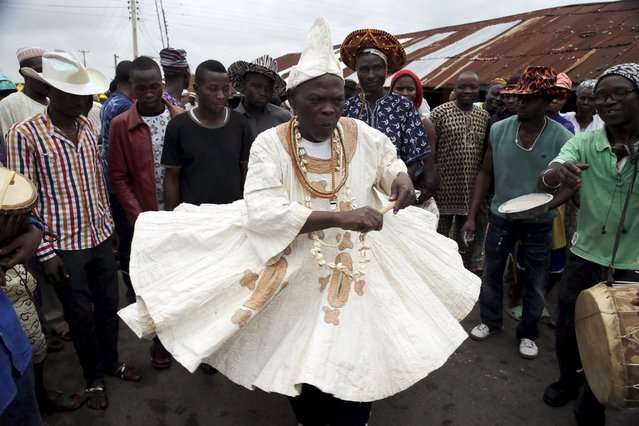A worshipper of the Osun river goddess dances down a street during the traditional town cleansing procession at the start of the annual Osun festival in Osogbo in Nigeria's southwest, August 10, 2015. (Photo by Akintunde Akinleye/Reuters)
