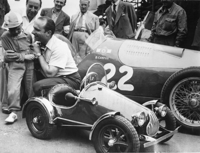Argentinian race driver Juan Manuel Fangio tries to comfort little Claudio Giorgi, who is crying bitterly after he wasn't allowed to drive around the race track in Fangio's Maserati. Claudio Giorgi is well known in Rome where he is seen frequently driving around in his miniature 46 cc race car. Fangio was racing June 2, 1949 at the 10th Grand Prix of Rome. The race car in the rear belongs to Benedicto Campos who also belongs to the Argentinian race team. (Photo by AP Photo)