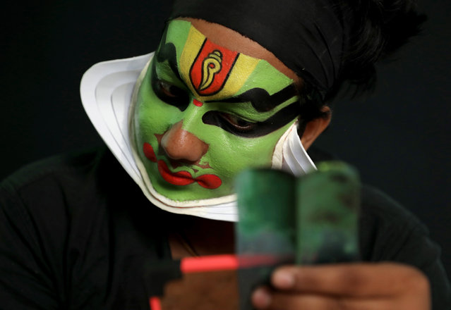 A South Indian dancer puts finishing touches to his make up as he gets ready to performs a traditional dance during a promotion event for Indian tourism in the Kerala state, in Kolkata, Eastern India, 28 January 2020. (Photo by Piyal Adhikary/EPA/EFE)