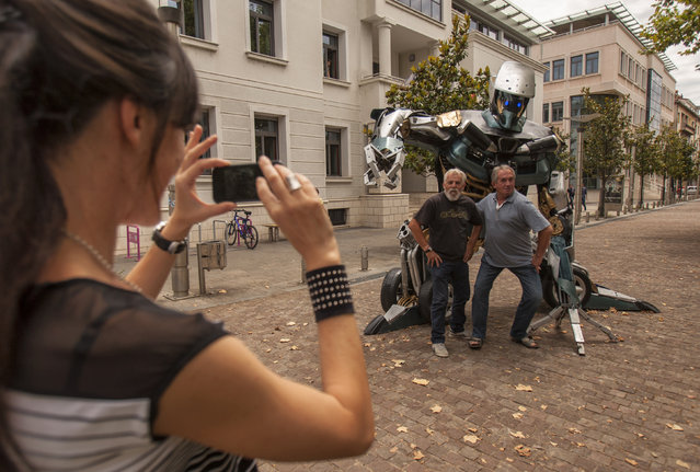 "A woman takes a picture of people posing in front of ""Zinzow"", a ""Transformers-inspired"" sculpture constructed from scrap metal in Podgorica, July 22, 2014. Danilo Baletic, 22, makes sculptures of his childhood cartoon heroes, ""Transformers"", from scrap metal. In the last two years he has made seven ""Transformers"" sculptures that are placed on the streets of Montenegro's capital Podgorica as part of an exhibition called ""Transformers defending Podgorica"". (Photo by Stevo Vasiljevic/Reuters)"