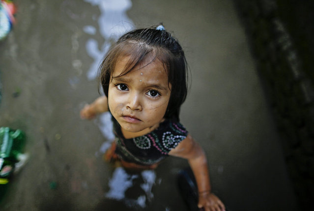 A girl stands amid floodwaters at her flooded home in a squatters' area after heavy rains in Kathmandu, Nepal, 17 August 2015. (Photo by Narendra Shrestha/EPA)