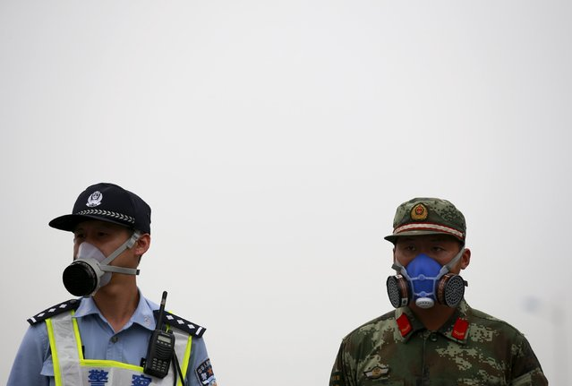 A paramilitary policeman and a policeman, both wearing masks, stand guard at a location within a 3-km (2-mile) exclusion zone from last week's explosion site in Binhai new district in Tianjin, China, August 18, 2015. (Photo by Kim Kyung-Hoon/Reuters)