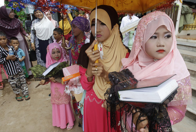 Muslims participate in Eid al-Fitr prayers along the Mekong river of Tanong, northeast of Phnom Penh, Cambodia, Wednesday, July 6, 2016. The Eid al-Fitr celebrations mark the end of the Muslim holy fasting month of Ramadan. (Photo by Heng Sinith/AP Photo)