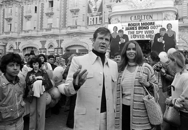 "In this May 20, 1977 file photo, Roger Moore, alias British secret agent James Bond, is accompanied by co-star Barbara Bach as they arrive for the screening of ""The Spy Who Loved Me"" at the Cannes Film Festival on the French Riviera. (Photo by AP Photo)"