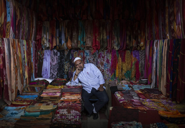 A Uyghur man waits for customers at his headscarf shop at a local market on August 2, 2014 in Kashgar, Xinjiang Province, China. (Photo by Kevin Frayer/Getty Images)