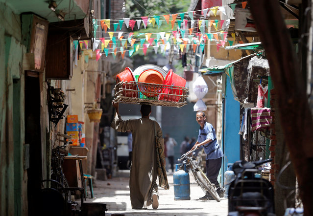 An Egyptian street vendor carries plastic dishes on a street decorated for the holy month of Ramadan in old Cairo, Egypt June 1, 2016. (Photo by Amr Abdallah Dalsh/Reuters)
