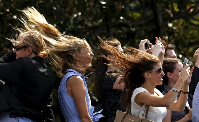 Guests, with their hair blown back, watch while Marine One takes off as U.S. President Barack Obama departs the White House in Washington August 27, 2015. Obama is traveling to New Orleans to commemorate the 10th anniversary of Hurricane Katrina. (Photo by Kevin Lamarque/Reuters)