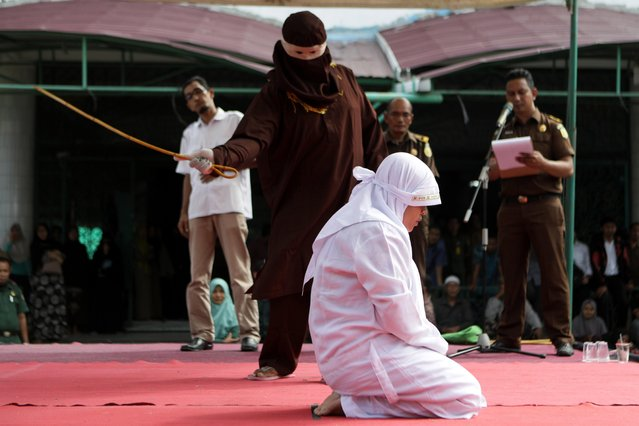 An Acehnese woman is whipped as punishment in front of the public in Banda Aceh, Indonesia, 11 September 2017. Reports state 11 Acehnese were sentenced 10 to 29 strokes of the whip for adultery and gambling in Aceh. Whipping punishment is one of the punishments for those who break the Sharia law in Aceh as it's the only one province in Indonesia which implemented the Sharia law as a positive law. (Photo by Hotli Simanjuntak/EPA/EFE)