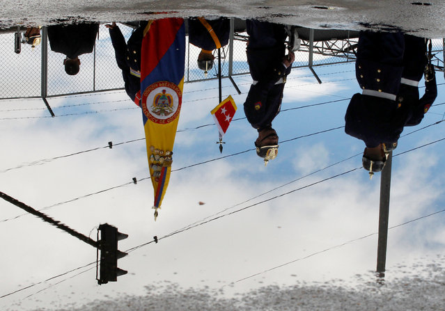 Soldiers are reflected in a puddle during a military parade to celebrate the 206th anniversary of Colombia's independence in Bogota, Colombia, July 20, 2016. (Photo by John Vizcaino/Reuters)