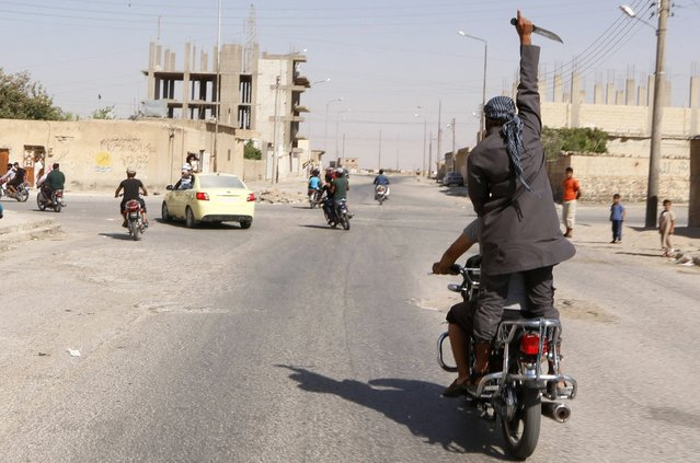 A man holds up a knife as he rides on the back of a motorcycle touring the streets of Tabqa city with others in celebration after Islamic State militants took over Tabqa air base, in nearby Raqqa city August 24, 2014. (Photo by Reuters/Stringer)