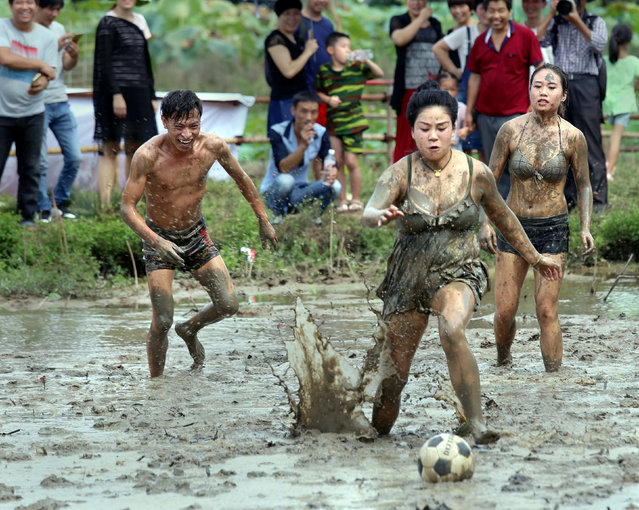 People fight for the ball as they take part in a mud football match during a festival for celebrating harvest in a village in Jinhua, Zhejiang Province, China September 24, 2017. (Photo by Reuters/China Stringer Network)