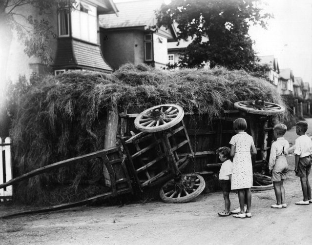 A group of children gather to look at an overturned hay cart in Cardiff. 3rd September 1936. (Photo by Richards/Fox Photos)