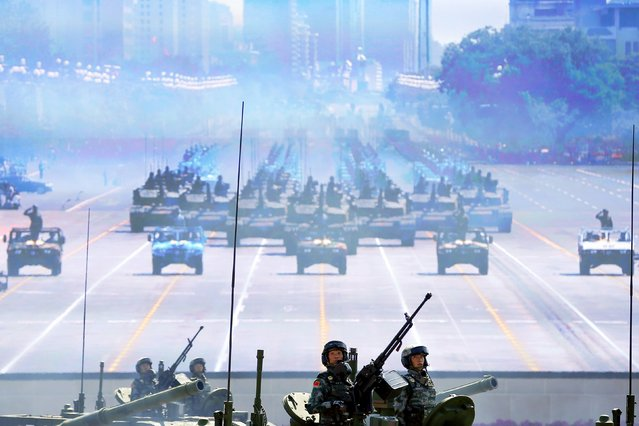 Soldiers of the People's Liberation Army (PLA) of China roll on their armoured vehicles to Tiananmen Square as others are shown on a big screen during the military parade marking the 70th anniversary of the end of World War Two, in Beijing, China, September 3, 2015. (Photo by Damir Sagolj/Reuters)