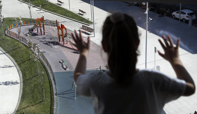 A girl looks at a deserted playground from her window in Bilbao, northern Spain, 23 April 2020. The Spanish government announced that starting from 26 April 2020, under 14-year-old children will be able to leave their confinement accompanied by an adult one hour a day. Spain is under lockdown to avoid the spread of the pandemic COVID-19 disease caused by the SARS-CoV-2 coronavirus. (Photo by Luis Tejido/EPA/EFE)