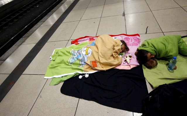 Two children of a Syrian family sleep on a platform after they arrived on a train from Budapest's Keleti station at the railway station of the airport in Frankfurt, Germany, early morning September 6, 2015. (Photo by Kai Pfaffenbach/Reuters)