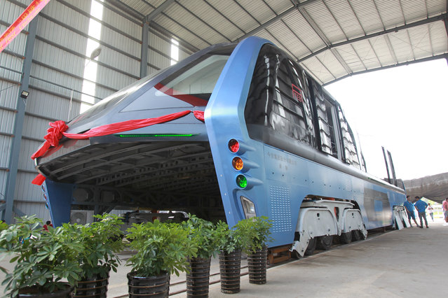 A model of an innovative street-straddling bus called Transit Elevated Bus is seen after a test run in Qinhuangdao, Hebei Province, China, August 3, 2016. The test bus currently consists of one segment, and is capable of carrying 300 people, according to local media. (Photo by Reuters/Stringer)