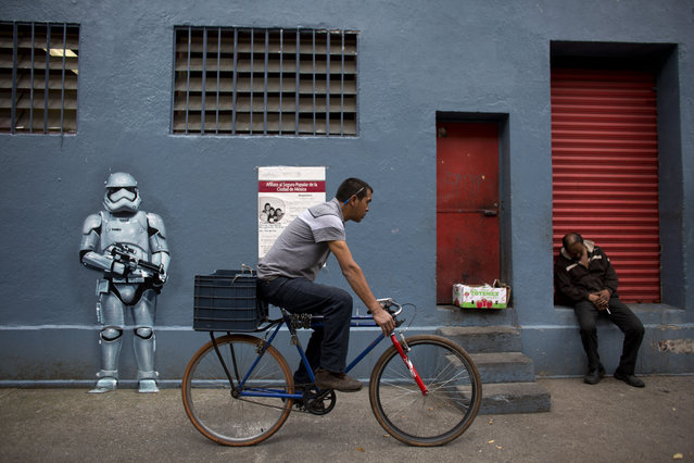 In this September 1, 2015 photo, a cyclist passes a storm trooper mural painted by a Street Art Chilango member artist Andrik Figueroa Barreto, also known as Andrik Noble, outside Michoacan Market in the Condesa neighborhood of Mexico City. Though many artists started as graffiti taggers, group members can now earn a living from splashing walls with their paint. (Photo by Rebecca Blackwell/AP Photo)