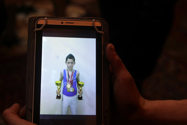 Gymnast Ahmad al-Sawas shows a picture, which he says was taken during his participation in the International Sports Games in the Sakha Republic in 2012, as his sits inside his home in the rebel-held Bustan al-Qasr neighbourhood of Aleppo, Syria March 23, 2016. (Photo by Abdalrhman Ismail/Reuters)