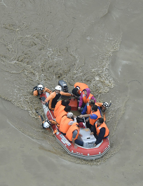 Residents are rescued by boat  from a flooded residential area in Joso, Ibaraki prefecture, northeast of Tokyo Thursday, September 10, 2015. (Photo by Kyodo News via AP Photo)
