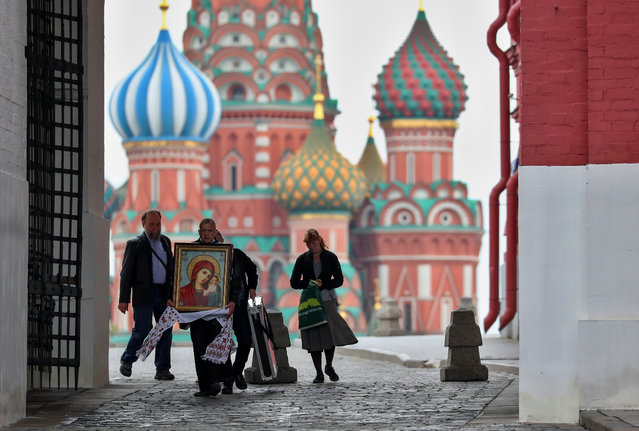 A man carries an icon near St. Basil's Cathedral amid the outbreak of the coronavirus disease (COVID-19) in Moscow, Russia May 6, 2020. (Photo by Evgenia Novozhenina/Reuters)