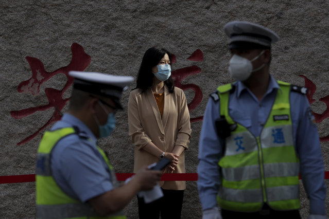 A teacher wearing a protective face mask to help curb the spread of the new coronavirus waits for arrival of the students outside a primary school in Beijing, Monday, June 1, 2020. With declining virus case numbers, students have gradually returning to their classes in the capital city. (Photo by Andy Wong/AP Photo)