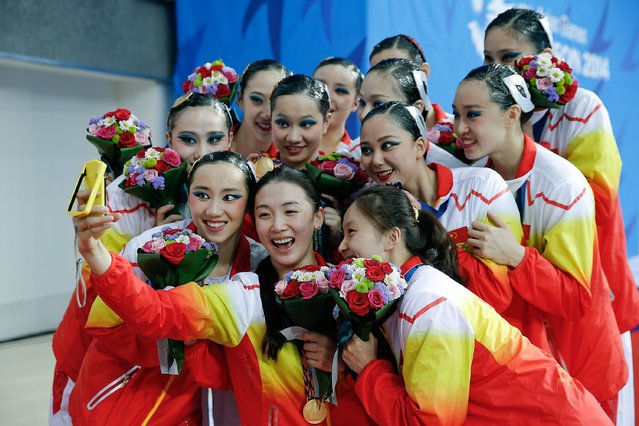 Gold medalist team of China pose for a selfie picture with their medals during the victory ceremony after the team synchronised swimming Free Combination - Final during the day four of 2014 Asian Games at Munhak Park Tae-hwan Aquatics Center on September 23, 2014 in Incheon, South Korea. (Photo by Lintao Zhang/Getty Images)