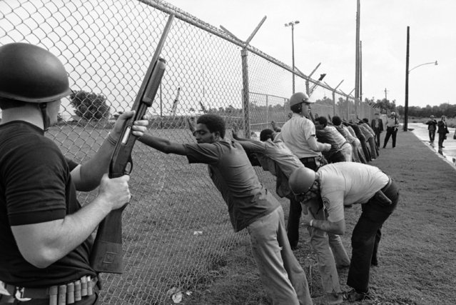 Police frisk young black youth lined up against a fence after they were arrested following a shootout between police and Black Panthers in New Orleans on Tuesday, September 15, 1970. (Photo by AP Photo)