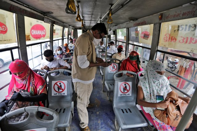 Indians board a city bus in Ahmedabad, India, Wednesday, June 10, 2020. India's coronavirus cases are spiking amid government reopening restaurants, shopping malls and religious places in most of its states after a more than 2-month-old lockdown. (Photo by Ajit Solanki/AP Photo)