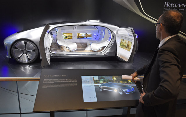 "A visitor looks at the ""F 015 Luxury in Motion"" autonomous driving vehicle at the Mercedes stand on the first press day of the Frankfurt Auto Show IAA in Frankfurt, Germany, Tuesday, September 15, 2015. (Photo by Jens Meyer/AP Photo)"