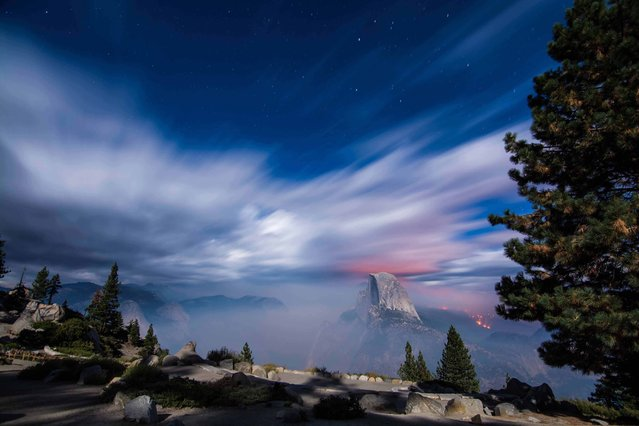 """""""Half Dome Yosemite large fire"""". This was taken at 3am with a 1 minute exposure showing Half Dome and the fire that was raging in the valley behind it. Photo location: Yosemite Glacier Point, CA. (Photo and caption by Judge Helbig/National Geographic Photo Contest)"""