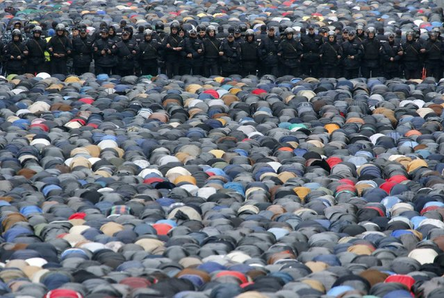 Russian Interior Ministry members stand guard as Muslims attend an Eid al-Adha mass prayer in Moscow October 4, 2014. Muslims around the world celebrate Eid al-Adha to mark the end of the haj pilgrimage by slaughtering sheep, goats, camels and cows to commemorate Prophet Abraham's willingness to sacrifice his son, Ismail, on God's command. (Photo by Sergei Karpukhin/Reuters)