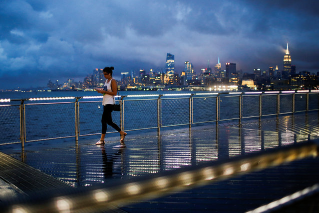 A woman walks on a bridge as low level cloud formation hovers over New York's Empire State Building and the skyline of midtown Manhattan as seen across the Hudson River in Hoboken, New Jersey, U.S., August 21, 2016. (Photo by Eduardo Munoz/Reuters)
