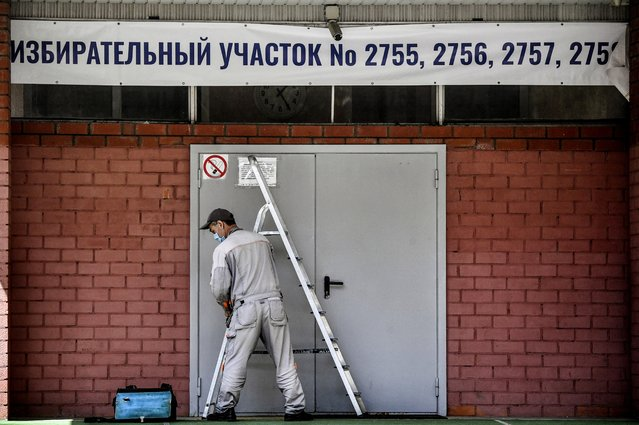 A worker fixes a banner at the entrance to a polling station in Moscow on June 23, 2020. Russians will vote on July 1 on a series of constitutional reforms allowing Vladimir Putin to potentially stay in power beyond 2024. A public vote on the reforms had been planned for April 22 but had to be postponed after Russia saw a surge in coronavirus cases. (Photo by Alexander Nemenov/AFP Photo)
