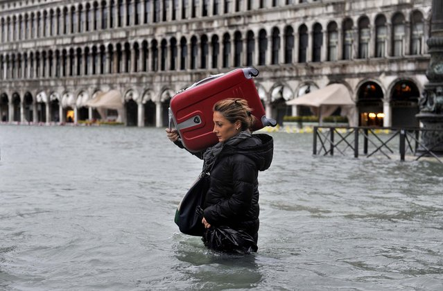 A tourist crosses flooded St. Mark's Square in Venice, Italy on November 11, 2012. Flooding is common this time of year and Sunday's level that reached a peak of 58.66 inches was below the 63 inches recorded four years ago in the worst flooding in decades. (Photo by Luigi Costantini/Associated Press)