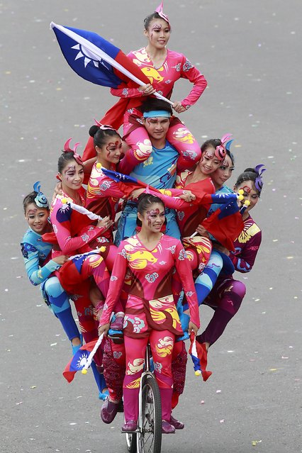 Dancers perform during Taiwan's National Day celebrations in front of the Presidential Office in Taipei October 10, 2014. Taiwan's president on Friday urged China to move toward a more democratic style of development, reiterating his strong support for pro-democracy demonstrations in Chinese-ruled Hong Kong. Ma Ying-jeou used his speech at Taiwan's National Day celebrations to discuss the island's own democratic development in remarks that appeared to show Beijing that Taiwan would never give up its own democracy and rule of law. (Photo by Pichi Chuang/Reuters)