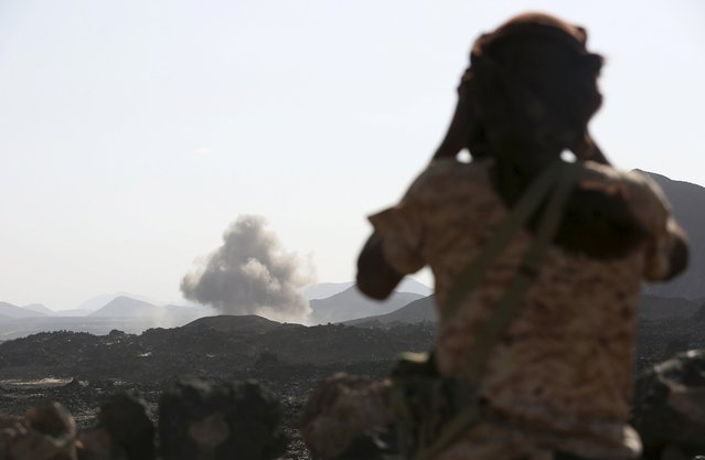 A soldier looks at smoke billowing from the site of a Saudi-led air strike on a Houthi position in the Yemeni frontline province of Marib September 15, 2015. (Photo by Reuters/Stringer)