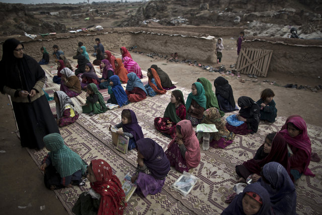 In this Tuesday, February 4, 2014, photo, Afghan refugee children repeat numbers displayed by their teacher during their class at a makeshift school set up in a mosque on the outskirts of Islamabad, Pakistan. (Photo by Muhammed Muheisen/AP Photo)