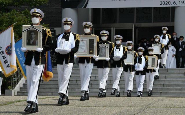 South Korean honour guards carry portraits and urns of compatriot soldiers killed during the 1950-53 Korean War, during a burial ceremony at the National Cemetery in Daejeon on June 19, 2020. Remains of four South Korean veterans, who were killed during the 1950-53 Korean War, were buried at a national cemetery ahead of the 70th anniversary of the war. The remains of three of the veterans were found last year on Arrowhead Ridge inside the Demilitarized Zone (DMZ) dividing the two Koreas. (Photo by Jung Yeon-je/AFP Photo)