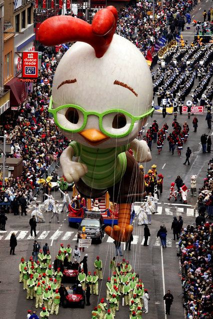 """The """"Chicken Little"""" balloon floats down Broadway during the Macy's Thanksgiving Day parade in New York, Thursday, November 24, 2005. (Photo by Jeff Christensen/AP Photo)"""